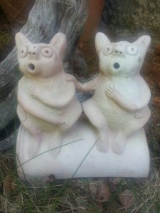Terra cotta toad house with two figures on top