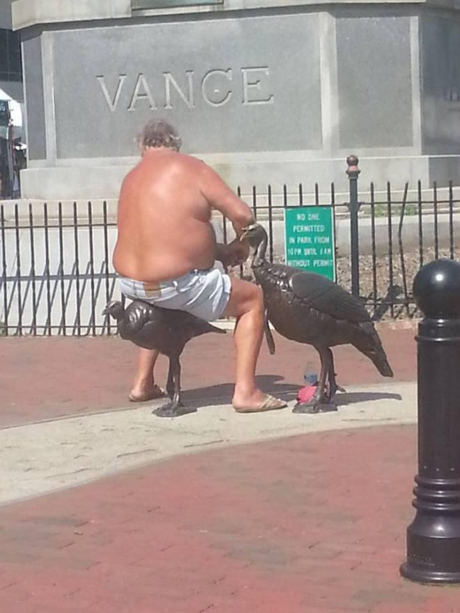 Shirtless man sitting astride a bronze turkey statue